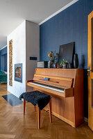 Klavier und Klavierhocker in offenem Wohnraum mit blauer Wand