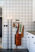 Candlesticks and leather apron in kitchen with white-tiled wall