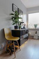 Gelber Stuhl und Rollschuhe vorm schwarzen Sideboard mit Beleuchtung