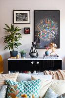 Bunte Deko, Zimmepflanzen und Bilder auf und überm Sideboard