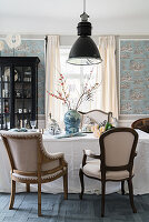 Stylish chairs, display cabinet and wallpaper in dining room
