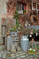 Vintage milk cans with Easter decorations, wooden houses and spring flowers