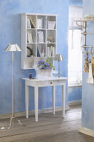 Console table below shelves mounted on pale blue wall