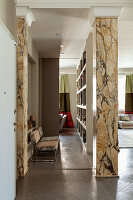 Designer chairs in corridor with marble pillars