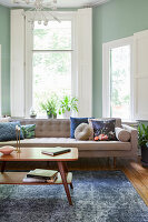 Retro furniture in living room with shutters and mint-green walls