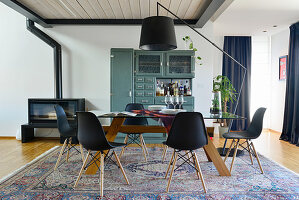 Black shell chairs around dining table in front of old dresser painted petrol blue