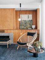 Runder Makramee-Sessel vor der Wohnwand aus Holz