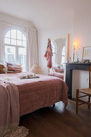 Doppelbett vor Rundbogenfenstern, großer Spiegel und stillgelegter Kamin im Schlafzimmer