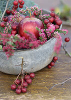 Metal bowl filled with haws, apples and heather