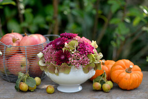 Flower arrangement of hydrangea, sedum and chrysanthemums surrounded by apples and pumpkins