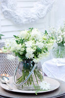 Bouquet of white aquilegia in polka-dot vase with handle