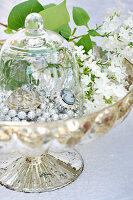 Jewellery under glass cover in bowl of lilac