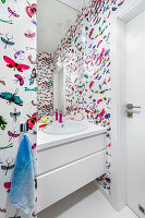 Wallpaper with pattern of butterflies an other insects in modern bathroom