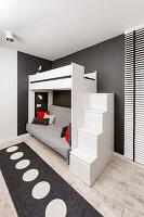 Treppe mit Stauraum zum Hochbett im Jugendzimmer in Schwarz-Weiß