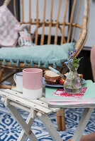 Sandwiches, coffee cups, magazines and vase of flowers on folding table outside