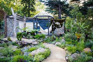 Steine und Pflanzen am Gartenweg entlang, im Hintergrund Terrassenplatz mit Hängematte