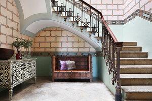 Schwarz-weiße Kommode und antike Holzbank in Treppenhalle