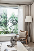 Rattan chair with cushion and standard lamp next to window with floor-length curtain