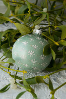 Christmas-tree bauble lying in mistletoe