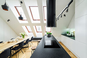 Island counter and dining table with black chairs in high-ceilinged room with skylights in sloping wall