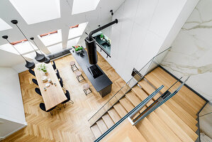 View down onto island counter, dining area and staircase in high-ceilinged room with skylights in sloping wall