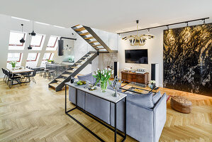 Console table against back of sofa in elegant interior with staircase and dining area in background