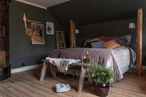 Box spring bed between rustic wooden columns below sloping ceiling