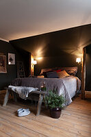 Box spring bed between rustic wooden columns below sloping ceiling lit by two wall-mounted lamps