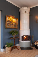Cylindrical, Scandinavian, tiled stove in corner next to antique landscape painting