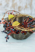 Old cake tin with wreath of twigs and Virginia creeper berries