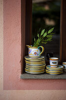 Stacked plates and jug with branch of bay leaves on windowsill