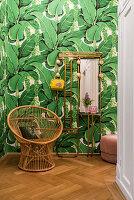 Rattansessel und Messing-Garderobe vor Tapete mit tropischem Blattmuster