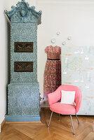 Kachelofen und rosa Stuhl vor Raumteiler mit Tapete im Schlafzimmer