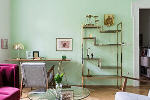 Messing-Regal und filigraner Tisch im Wohnzimmer mit grüner Wand