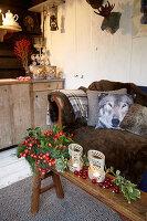 Holzbank mit Weihnachtsdekoration vor Sofa mit Kissen