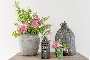 Lilac and spirea in antique vase and lanterns on wooden table