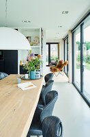 Long oak dining table in open-plan interior with glass wall overlooking garden