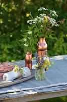 Sommerliche Wiesenblumensträuße in kupferfarbenen Gefäßen auf Tisch im Freien