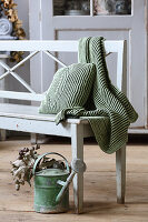 Knitted, ribbed cushion and blanket in autumnal green