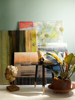 Paintings leaning against wall behind sculptures and plants