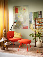 Painting on wall above orange armchair and matching footstool