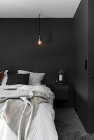 Schlafzimmer mit schwarzen Wänden und Glühbirne als Hängeleuchte