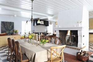 Large country-house kitchen-dining room with dining table next to open fireplace