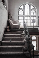 Carpet on staircase with armchair on landing with arched window in old factory