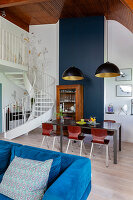 Blue velvet sofa, table in dining area and antique dresser in maisonette apartment
