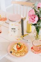 Waffel mit Früchten auf festlich gedecktem Tisch mit Kerze und Pfingstrosenstrauß