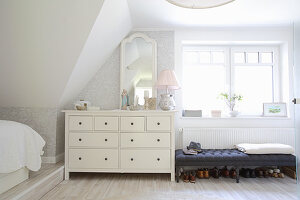 Chest of drawers and bench in bright bedroom