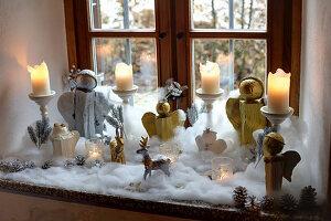 DIY-Weihnachtsengel und Kerzen umgeben von Schneewatte auf Fensterbank