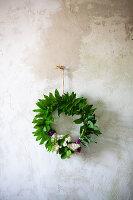 Kranz aus Fliedern und Maiglöckchenblättern an der Wand