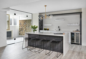 Bar with connected glass doored wine cellar and black bar stools in a modern style basement